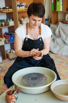 Mistrz garncarstwa pokazuje, jak pracować z gliną i kołem garncarskim. produkcja rękodzieła.