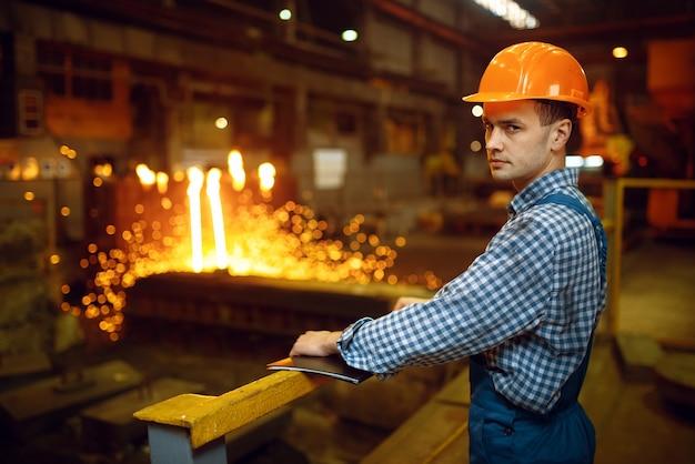 Mistrz hutnictwa w hełmie w piecu z ciekłym metalem, huta stali, przemysł metalurgiczny lub metalurgiczny, przemysłowa produkcja żelaza na walcowni