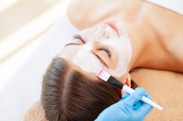 Mistrz i klient w gabinecie kosmetycznym, maska z białej glinki do pielęgnacji skóry twarzy