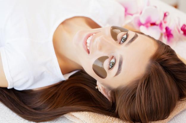 Mistrz i klient w gabinecie kosmetycznym, plastry do pielęgnacji skóry pod oczami