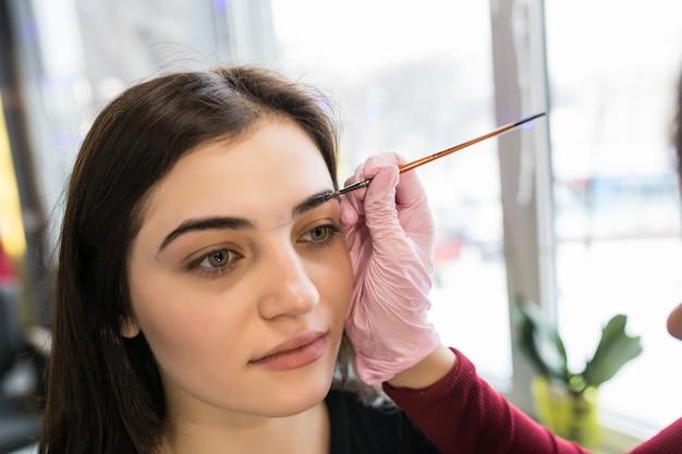 Mistrz kobieta umieściła farbę do brwi w salonie piękności podczas makijażu