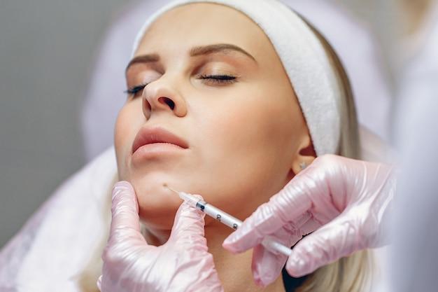 Mistrz kosmetologa wykonujący zastrzyki z botoksu przeciwstarzeniowego pięknej, atrakcyjnej kobiecie o gładkiej skórze.