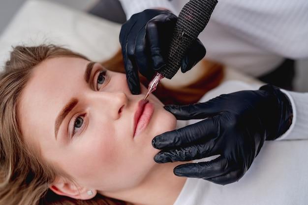 Mistrz makijażu permanentnego konturowanie ust w gabinecie kosmetycznym