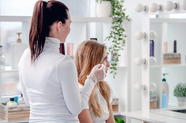 Mistrz makijażu permanentnego pokazuje klientce efekty mikrobladingu brwi i tatuażu ust