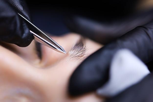 Mistrz makijażu permanentnego przygotowuje brwi klientki do zabiegu wyrywania włosków pęsetą