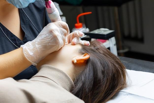 Mistrz makijażu permanentnego siada u wezgłowia łóżka i wykonuje zabieg tatuowania powiek