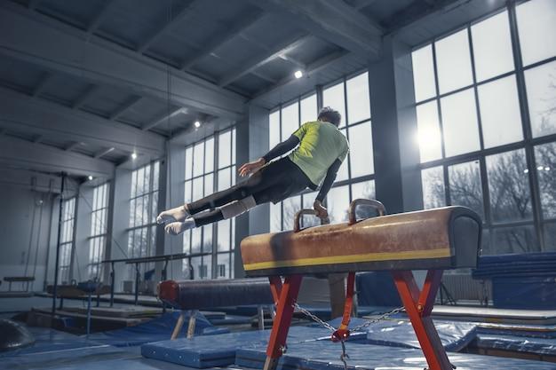 Mistrz. mały mężczyzna gimnastyczka trening na siłowni, elastyczny i aktywny
