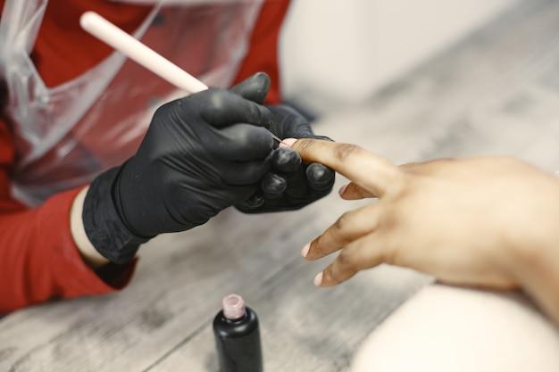 Mistrz manicure. afrykańska kobieta. salon piękności.