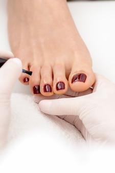 Mistrz manicure maluje na kobiecych paznokciach bordowym lakierem do paznokci pędzlem w białych rękawiczkach