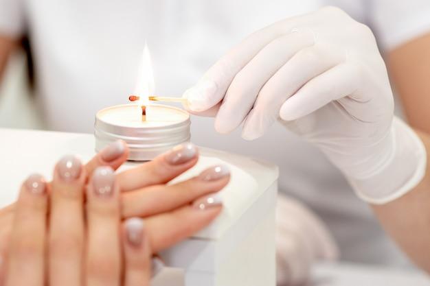 Mistrz manicure w białych rękawiczkach zapalający świecę z zapałką w salonie paznokci