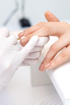 Mistrz manicure w ochronnych rękawiczkach nakładający beżowy lakier na kobiece paznokcie w gabinecie kosmetycznym