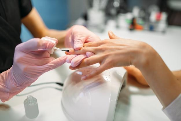 Mistrz manicure w różowych rękawiczkach nakładający lakier do paznokci klientce