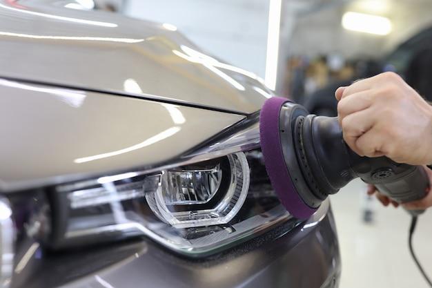 Mistrz mechanik polerujący reflektory samochodu w warsztacie za pomocą maszyny wysokiej jakości samochodu zbliżenie