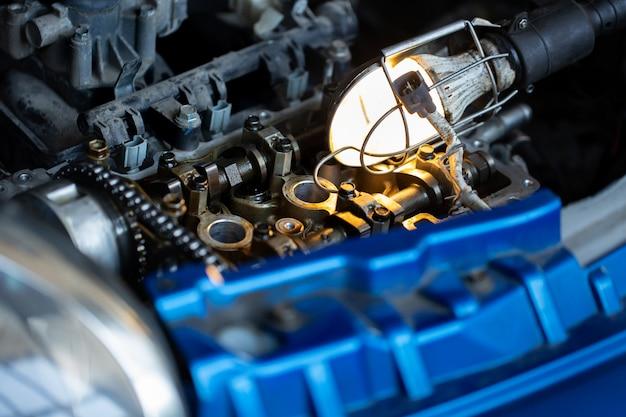 Mistrz mechanik samochodowy naprawia silnik samochodu na stacji paliw