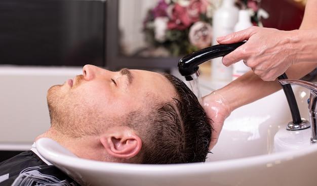 Mistrz myje głowę klienta w sklepie fryzjerskim, fryzjer robi fryzurę dla młodego mężczyzny.