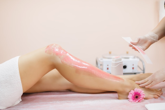 Mistrz nakłada różowy wosk do depilacji na nogę młodej kobiety w celu usunięcia owłosienia