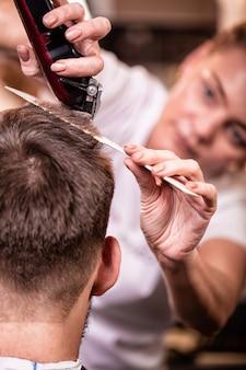 Mistrz obcina włosy i brodę mężczyzny w zakładzie fryzjerskim, fryzjer robi fryzurę dla młodego mężczyzny. koncepcja piękna, dbałość o siebie.