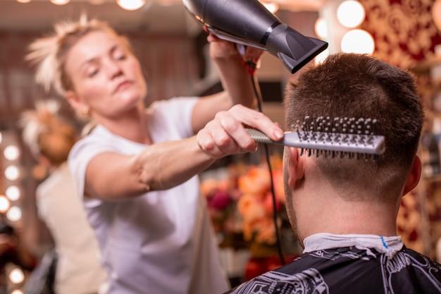 Mistrz obcina włosy i brodę mężczyzny w zakładzie fryzjerskim, fryzjer robi fryzurę dla młodego mężczyzny.