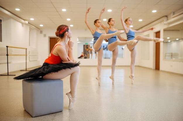 Mistrz patrzenia na występy młodych baletnic na zajęciach. szkoła baletowa, tancerki na lekcji choreografii, dziewczyny ćwiczące taniec gracji