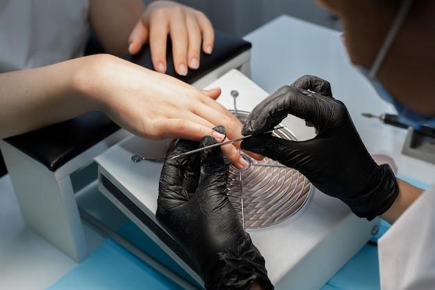Mistrz piłuje swoje paznokcie piłą. dziewczyna na manicure w salonie. zbliżenie