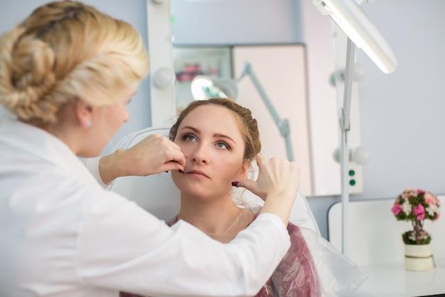 Mistrz poprawia makijaż, nadaje kształt i nić wyrywa brwi w salonie kosmetycznym. profesjonalna pielęgnacja twarzy