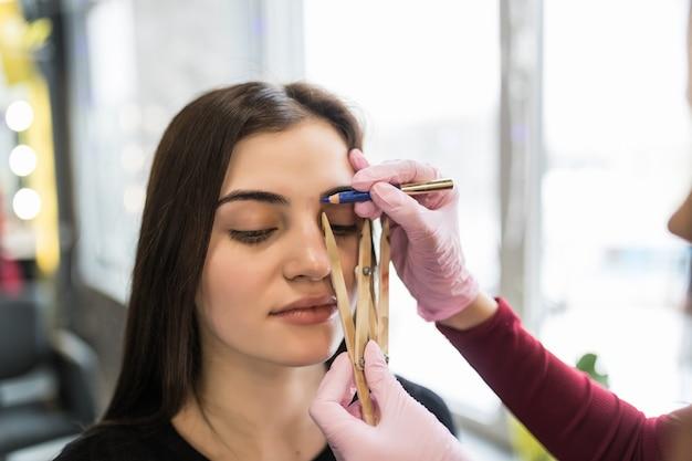 Mistrz pracuje nad techniką brwi w nowoczesnym salonie kosmetycznym