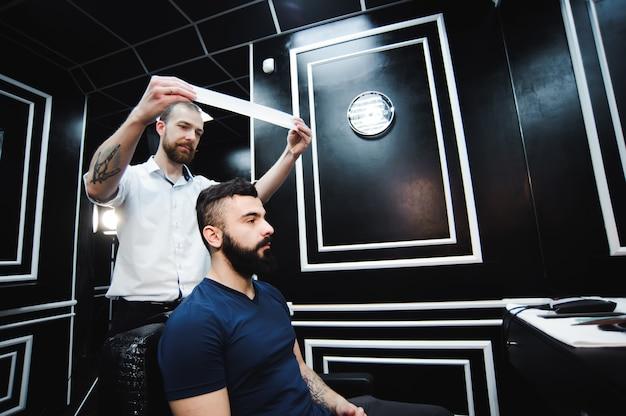 Mistrz przycina włosy i brodę mężczyzn w salonie fryzjerskim, fryzjer robi fryzurę dla młodego mężczyzny.