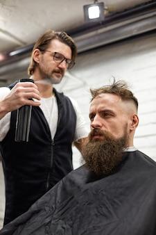 Mistrz przycina włosy i brodę mężczyzn w salonie fryzjerskim, fryzjer robi fryzurę dla młodego mężczyzny