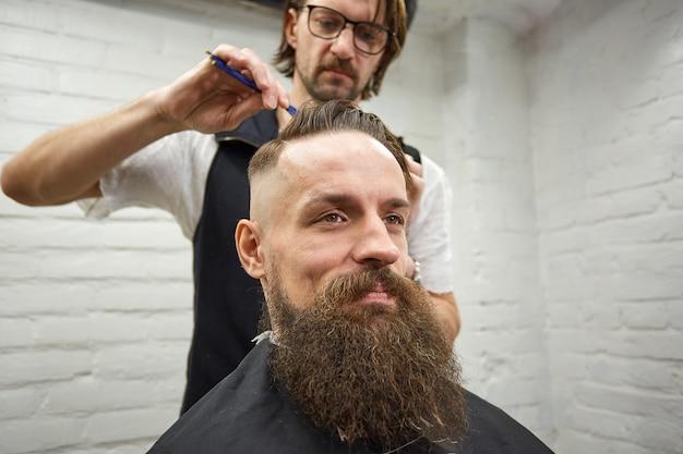 Mistrz przycina włosy i brodę mężczyzn w zakładzie fryzjerskim