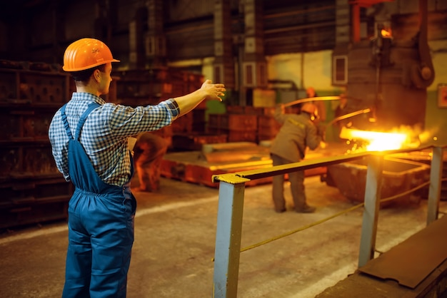 Mistrz przygląda się procesowi wytwarzania stali w piecach, hutach, przemyśle metalurgicznym lub metalurgicznym, produkcji przemysłowej produkcji metali na walcowni