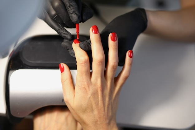 Mistrz robi czerwony manicure do klienta w salonie piękności zbliżenie close