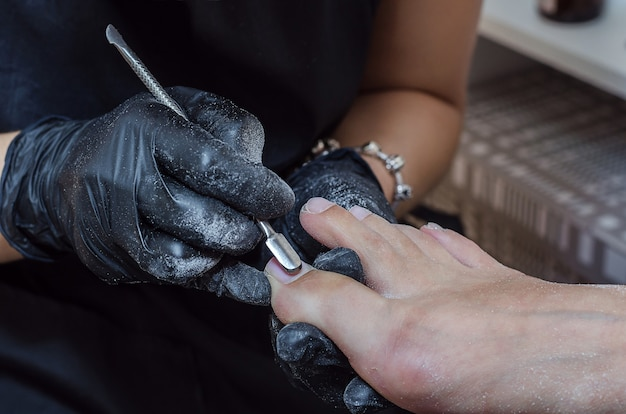 Mistrz robi pedicure sprzętowy w studio