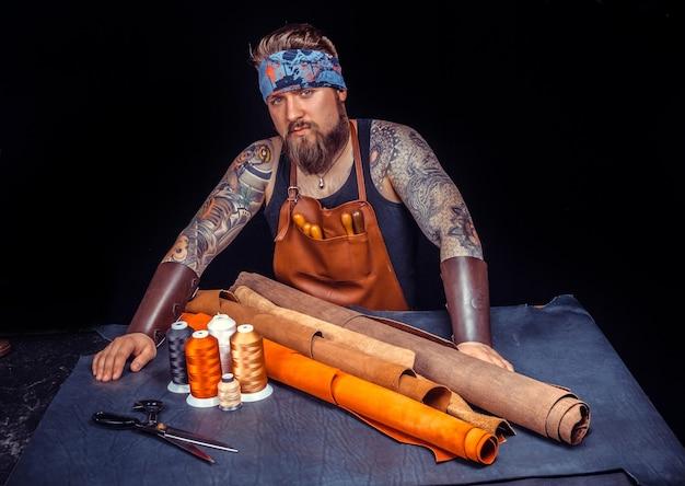 Mistrz rzemieślniczy wykonujący galanterię skórzaną w warsztacie