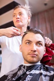 Mistrz ścina męskie włosy w salonie. nożyczki, zbliżenie roschetsk. fryzjerstwo koncepcyjne, strzyżenie, uroda.