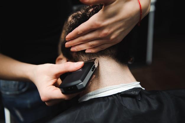 Mistrz ścina włosy i brodę mężczyzn w zakładzie fryzjerskim, fryzjerskim