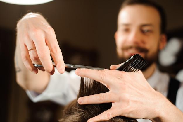 Mistrz ścina włosy i brodę mężczyzn w zakładzie fryzjerskim