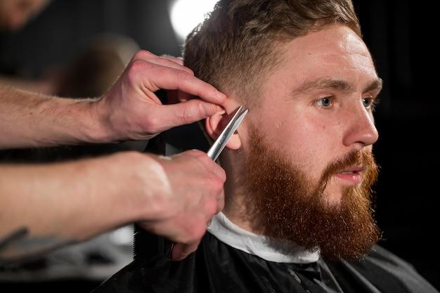Mistrz ścina włosy i brodę w sklepie fryzjerskim. fryzjer robi fryzurę za pomocą nożyczek i metalowego grzebienia.