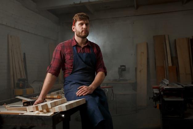 Mistrz stolarski w koszuli i fartuchu w warsztacie