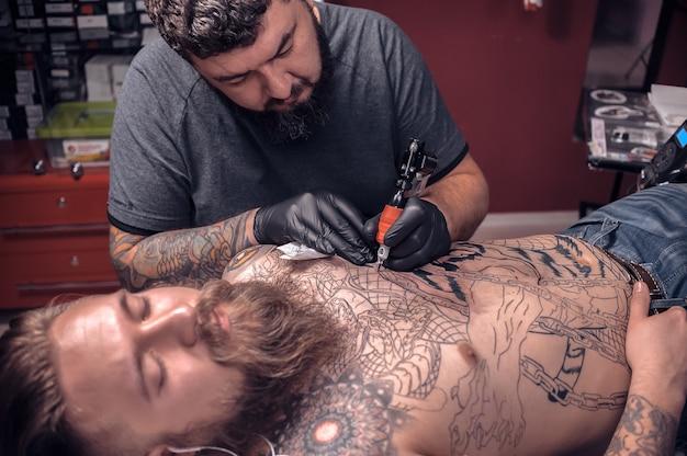 Mistrz sztuki tatuażu podczas pracy w studio tatuażu