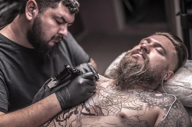 Mistrz sztuki tatuażu pokazujący proces wykonywania tatuażu