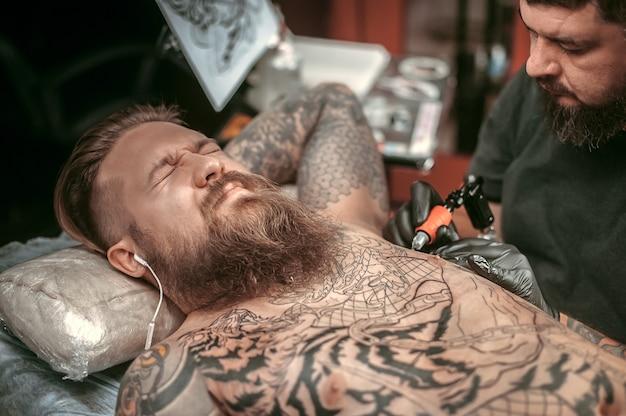 Mistrz sztuki tatuażu pokazuje tatuaże w salonie.