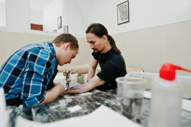 Mistrz tatuażu wykonuje tatuaż dla człowieka rocka