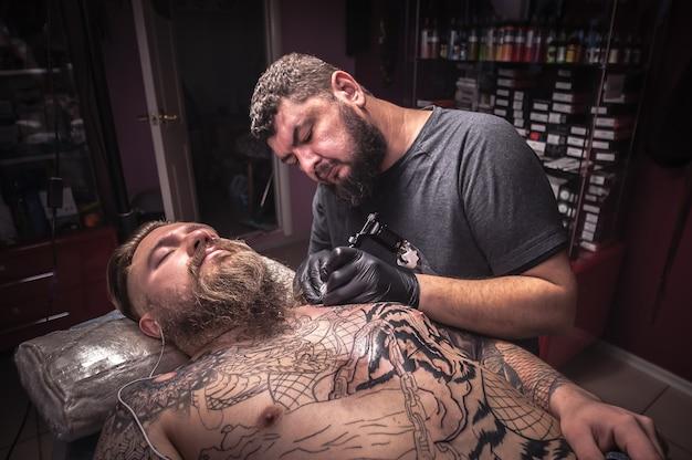Mistrz tatuażu wykonuje tatuaż u klienta.