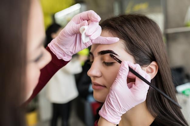Mistrz w białych rękawiczkach pracuje przy czarnych brwiach w salonie piękności