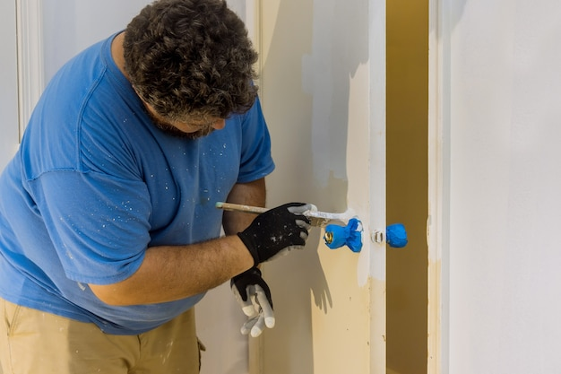 Mistrz wykonawcy przetwarza malarza malując drewniane drzwi za pomocą pędzla w domu