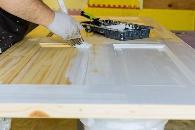 Mistrz wykonawcy przetwarza malarza malując drewniane drzwi za pomocą pędzla w nowym domu