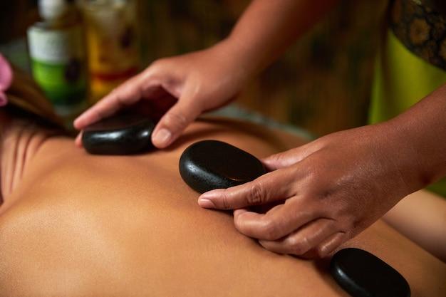 Mistrz wykonuje masaż pleców za pomocą specjalnych magnesów do zabiegów spa kamieni
