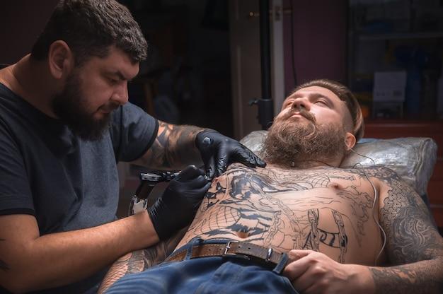 Mistrz wykonuje tatuaż na skórze swojego klienta w studio tatuażu