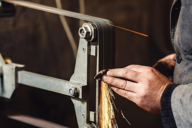 Mistrz z bliska szlifuje nóż na szlifierce taśmowej i wytwarza wiele iskier.