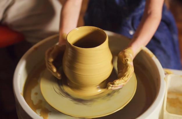 Mistrz z dzieckiem formuje gliniany dzbanek.